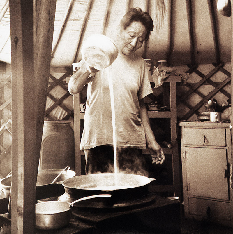 Photo of a woman cooking airag in a yurt in Mongolia