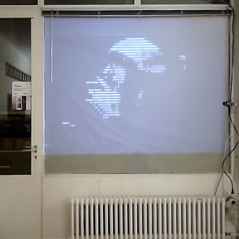 Photo of a man's image projected on the front window of Labo after being processed into ASCII