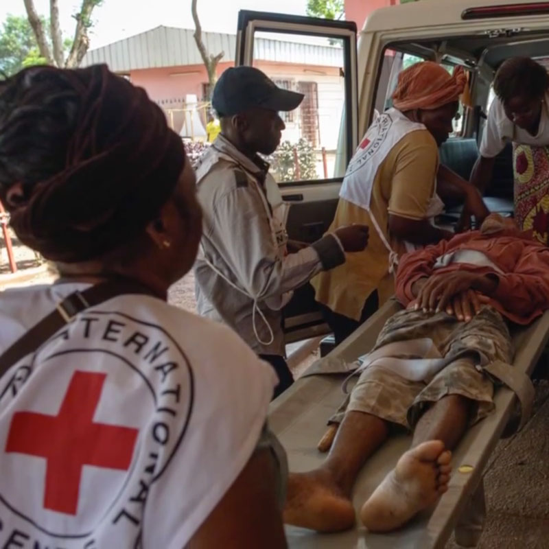 Photo of ICRC staff in Africa carrying a wounded out of an ambulance