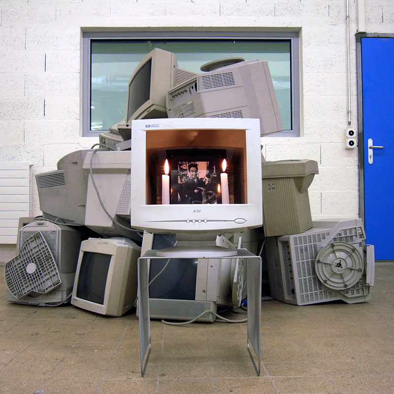 Photo of an empty CRT screen with two candles and a picture of Nam June Paik inside, in front of a pile of CRT screens