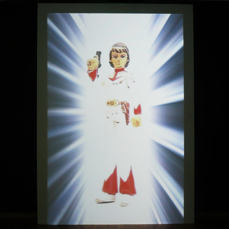 Photo of the video of a figurine of a man projected on a piece of wood